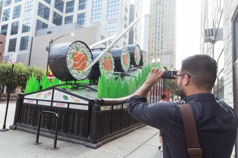 Man photographs GrubHub sushi ad campaign on top of Chicago CTA subway entrance