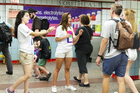 Representatives pass out vitaminwater farecards to CTA commuters