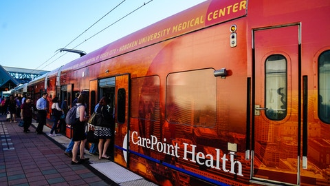 Commuters boarding NJ Transit train with CarePoint Health advertisement
