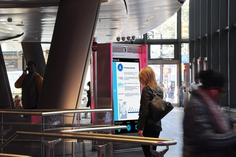 Woman finds transit information at Interactive Information Kiosk in New York subway