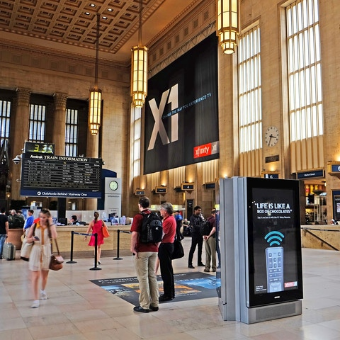 Travelers inside Philadelphia train Amtrak station with digital media