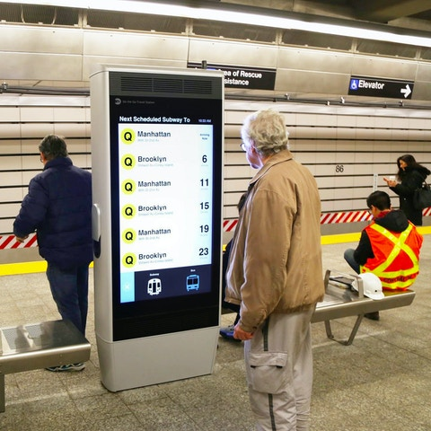 Man reading train schedule on Intersection's Interactive Information Kiosk in the New York City subway