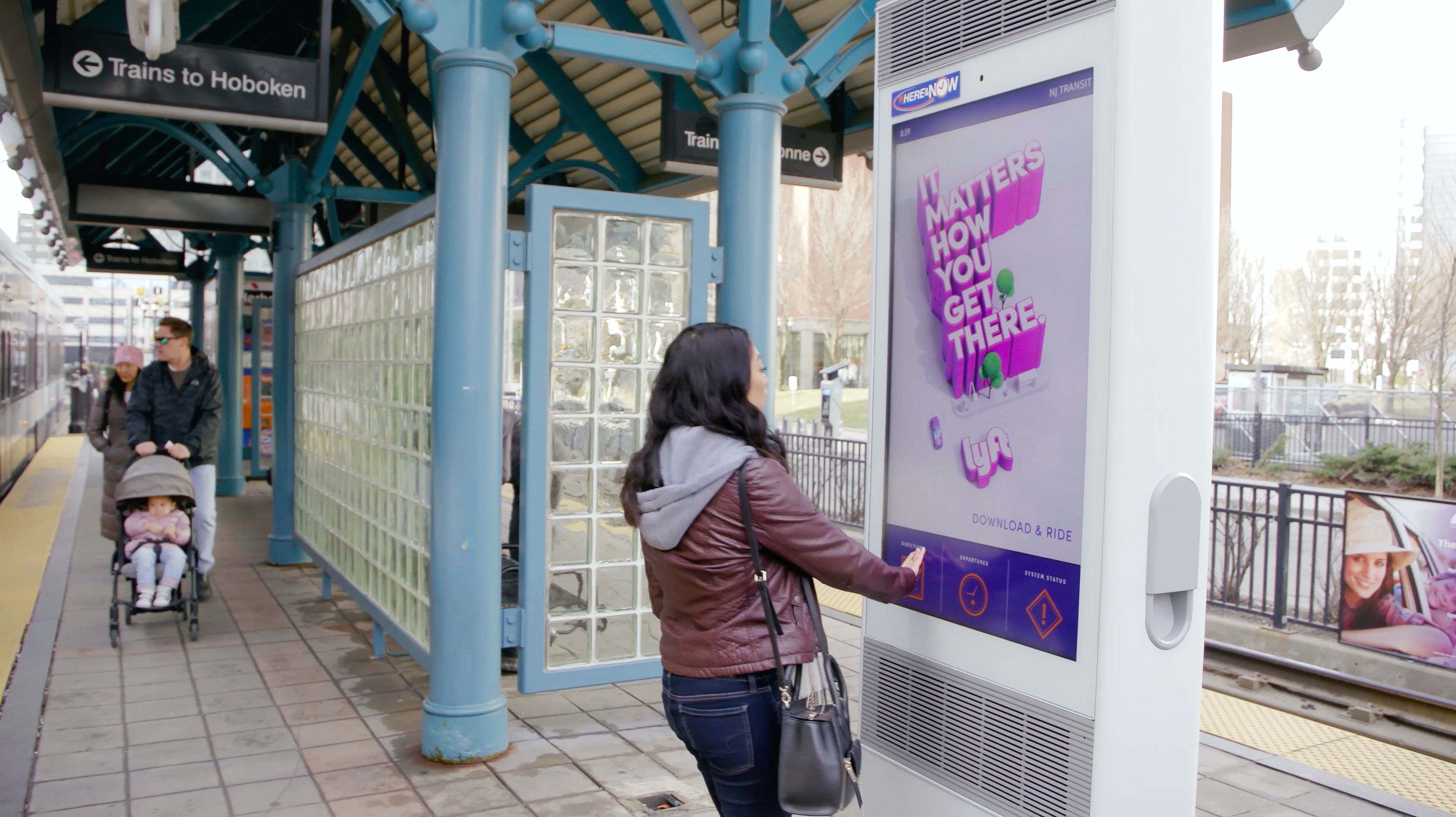Woman interacting with IxNTouch kiosk in NJ Transit station