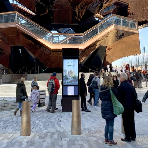 People walking by kiosk at Hudson Yards