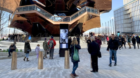 Visitors pass by kiosk with advertising at Hudson Yards