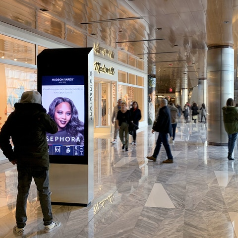 Visitor views advertisement and interacts with kiosk at Hudson Yards