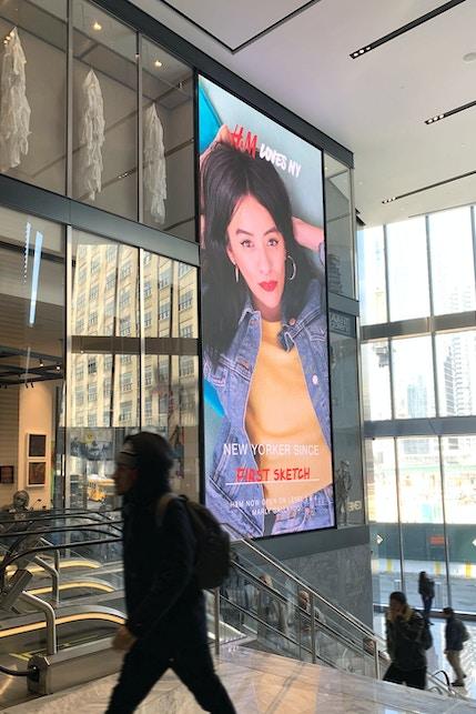 Visitors walk by large format digital display at Hudson Yards