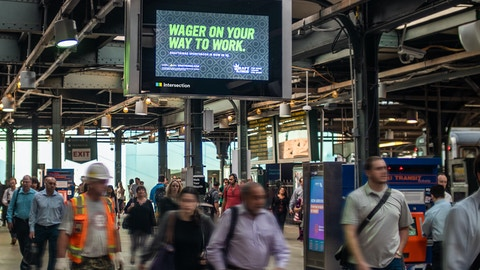 Commuters pass by dynamic digital DraftKings ad in NJTransit