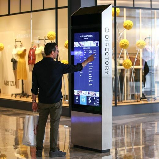 Shopper browses directory on IxNTouch kiosk at Hudson Yards