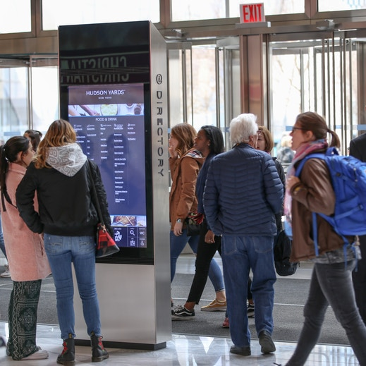 Visitors browse IxNTouch kiosk directory at Hudson Yards