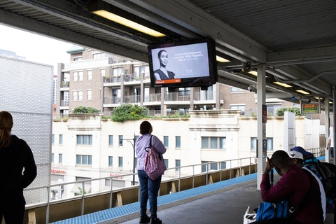 Rider looks at IxNSight display with advertising and arrival times in CTA