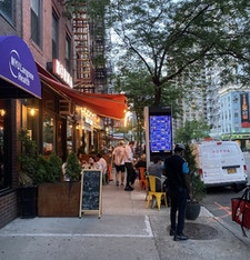 Link kiosk surrounded by outdoor diners in NYC