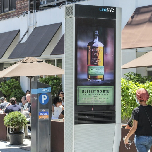 LinkNYC near people dining outdoors