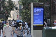 LinkNYC Kiosk displaying best times to visit grocery stores